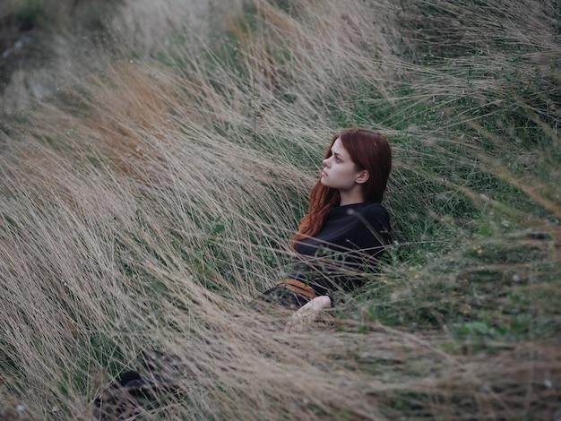 Romantische vrouw in zwarte jurk rood haar natuur droog gras herfst