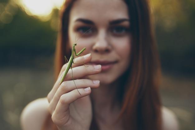 Romantische vrouw met bidsprinkhaan op haar hand buiten in de wei.
