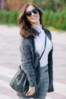 Romantische vrouw met donker kapsel in grijze jas genieten van buiten wandelen