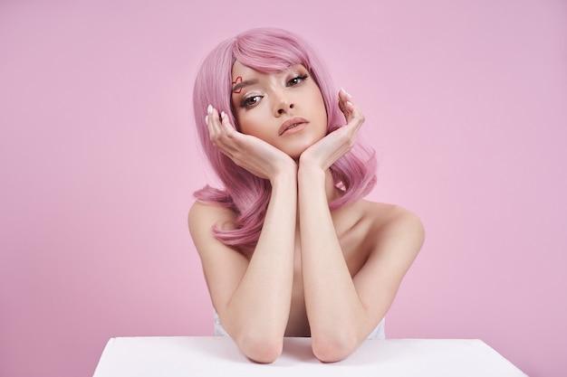 Romantische vrouw met geverfd roze haar aan tafel