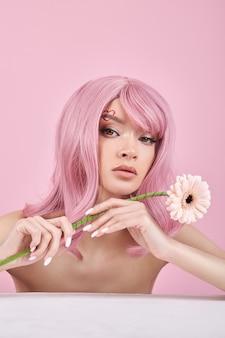 Romantische vrouw met geverfd roze haar houdt bloem vast