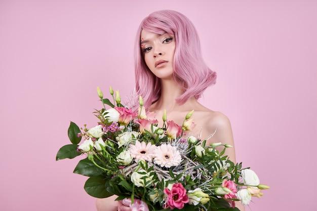 Romantische vrouw met geverfd roze haar houdt bloemen vast