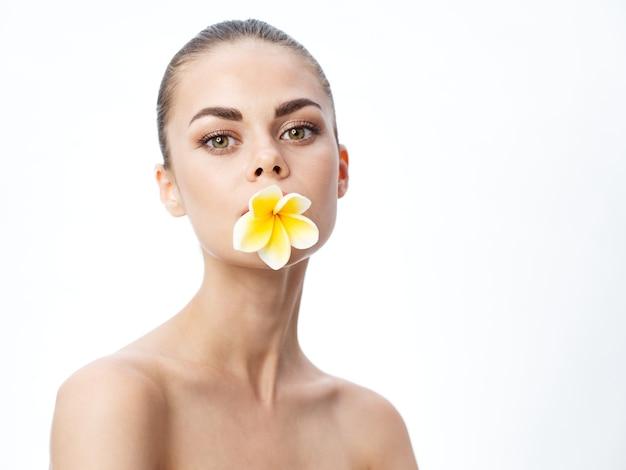 Romantische vrouw met kapsel op haar hoofd en bloem in haar tanden bijgesneden weergave