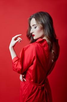 Romantische vrouw met lang blond haar in rode jurk, gladde schone huid