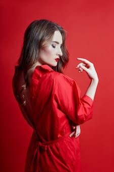 Romantische vrouw met lang blond haar in rode jurk