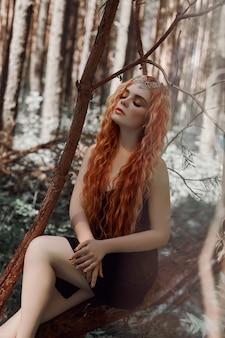 Romantische vrouw met rood haar, liggend in het gras in het bos