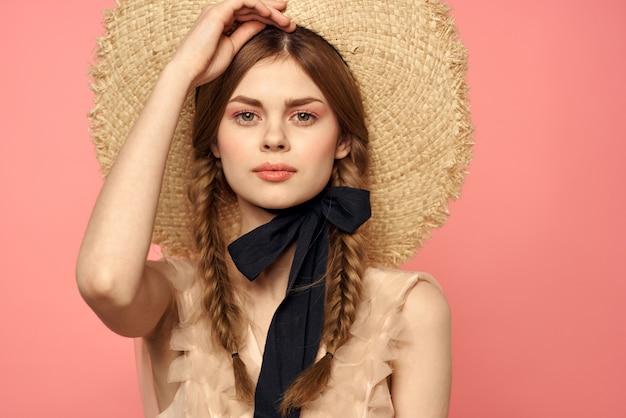 Romantische vrouw met vlechten en in een strooien hoed poseren