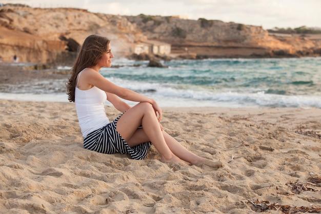 Romantische vrouw op een zonnige dag staren naar de zee
