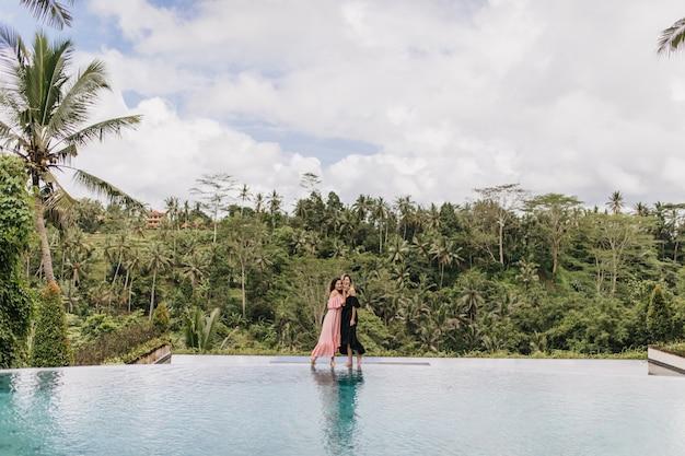 Romantische vrouwen in lange jurken poseren op prachtige natuur. buiten schot van gemiddelde lengte van vrouwen die tijd doorbrengen in het resort.