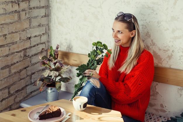 Romantische vrouwen zitten in café met bloemen in handen en kopje koffie