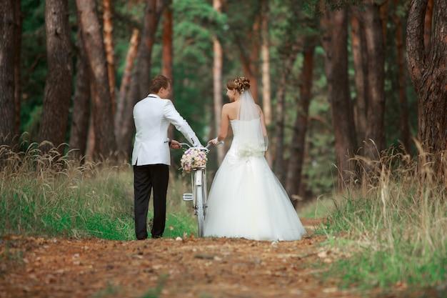 Romantische wandeling van bruid en bruidegom buitenshuis met fiets. gelukkige bruidspaar verliefd wandelen en kijken elkaar in de natuur met fiets. trouwdag in bos in de zomer. bruiloft