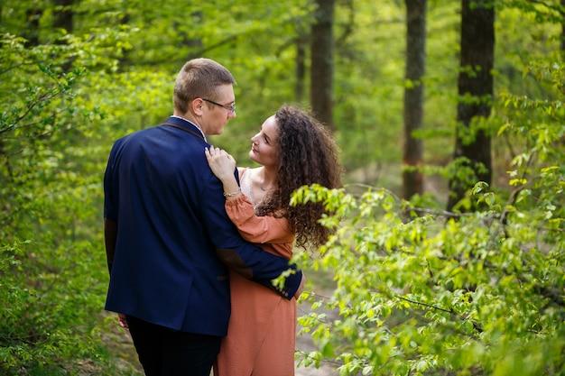 Romantische wandeling van een jong stel in een groen bos, warm lenteweer. jongen en meisje knuffelen in de natuur
