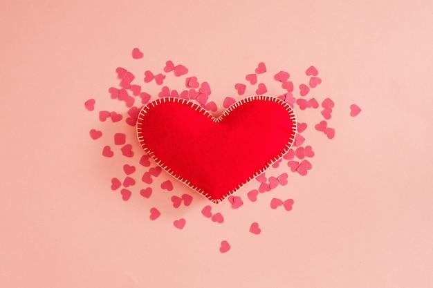 Romantische wenskaart. plat leggen van rood handgemaakt vilten hart op pastelroze