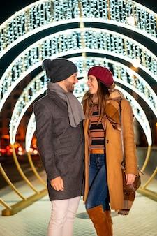 Romantische winterblindheid van een kaukasisch stel naast de kerstverlichting van de stad