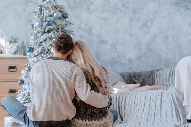 Romantische wintervakantie. achteraanzicht van vreedzame paar zittend op de vloer omarmen, dennenboom kijken ze ingericht.