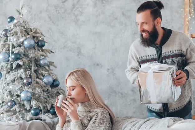 Romantische wintervakantie. guy bereid verrassingsgeschenk voor zijn vriendin. dame ontspannen op de bank, genietend van warme dranken.