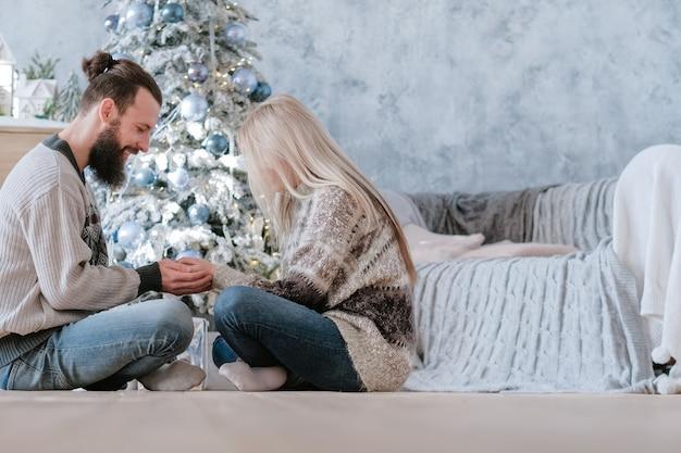 Romantische wintervakantie. zijaanzicht van paar zittend met gekruiste benen op de vloer, hand in hand
