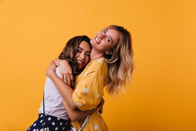 Romantische witte dame in gele jurk die haar zus omhelst. indoor portret van mooi trendy meisje chillen met beste vriend tijdens weekendportret.
