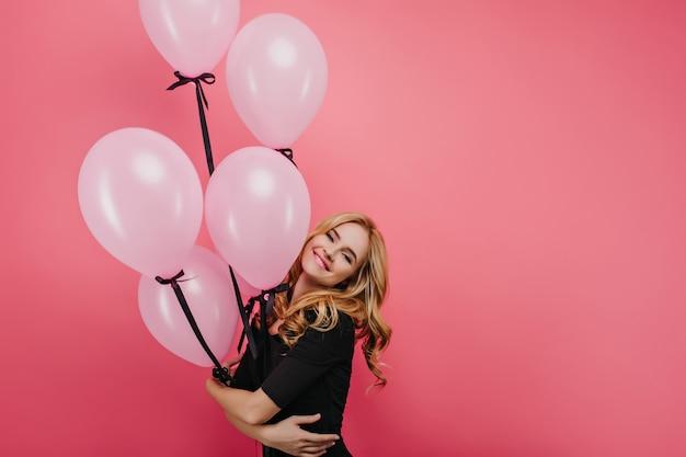 Romantische witte jonge dame met partij ballonnen genieten van verjaardag fotoshoot. dromerige blonde dame in stijlvolle zwarte kleding die op een evenement wacht.