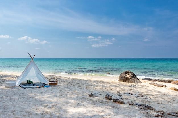 Romantische witte picknicktent op wit zandstrand met glashelder water en blauwe hemel