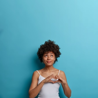 Romantische zorgzame tedere afro-amerikaanse vrouw drukt passie en romantiek uit, maakt hartgebaar, kijkt omhoog, gekleed in casual vest, geïsoleerd op blauwe muur, lege ruimte voor uw promotie