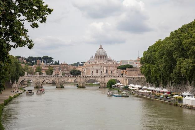 Rome, italië - 22 juni 2018: panoramisch uitzicht op de pauselijke basiliek van st. peter (st. peter's basilica) in het vaticaan en de rivier de tiber met brug in rome. zomerdag