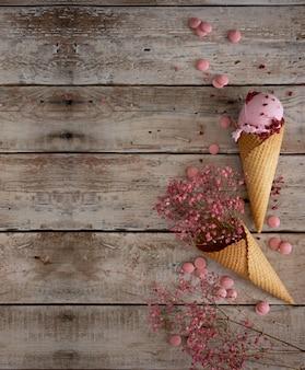 Romig frambozenijs met frambozenbessen en roze bloemen in een wafelkegel op een oude houten lijst