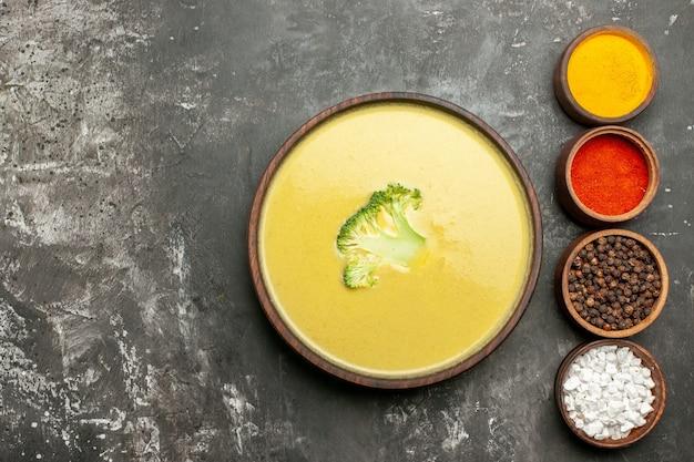 Romige broccolisoep in een bruine kom en verschillende kruiden aan de linkerkant van de grijze tafel