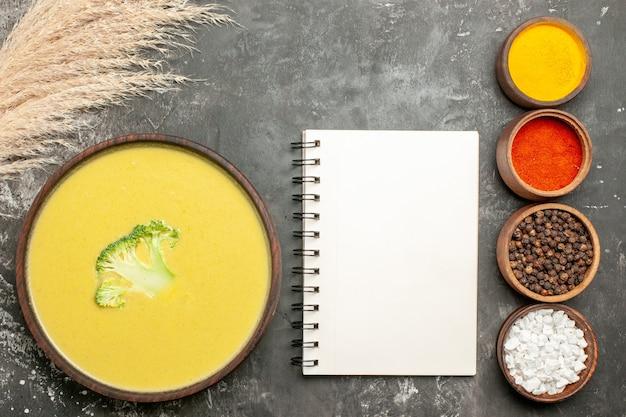Romige broccolisoep in een bruine kom en verschillende kruiden naast notitieboekje op grijze lijst
