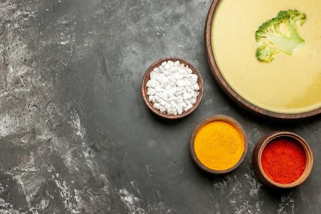 Romige broccolisoep in een bruine kom en verschillende kruiden op grijze lijst