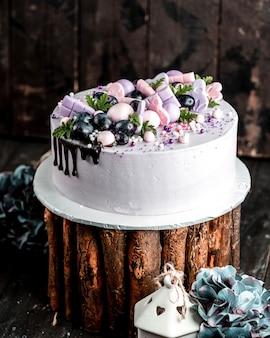 Romige cake in lila gegarneerd met roze lila decoraties en druiven