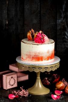 Romige cake in wit met rode decoratie gegarneerd met granaatappel en bloemen