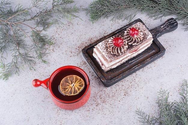 Romige cake op donker bord met kopje thee.