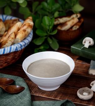 Romige champignonsoep in een witte kom
