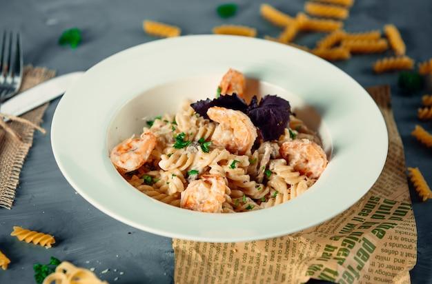 Romige fusilli pasta met gebakken garnalen en verse kruiden