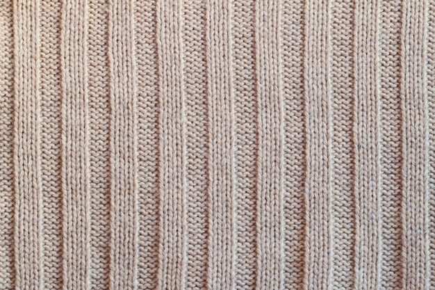 Romige gebreide wollen warme kleding voor de textuurachtergrond van de de winterstof