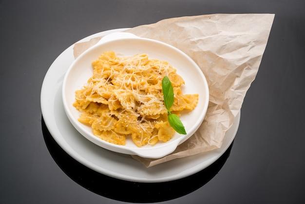 Romige, geroosterde pompoen-penne-pasta met parmezaanse kaas.