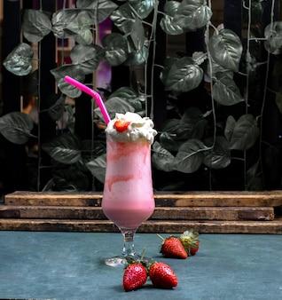 Romige melkachtige cocktail met aardbeiensiroop op de blauwe lijst