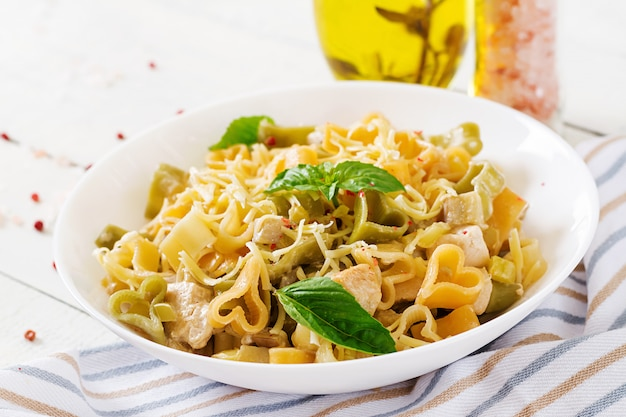 Romige pasta met kip en aubergine geserveerd in diepe plaat.