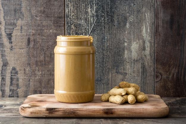 Romige pindakaas en lepel op houten