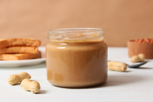 Romige pindakaas en pinda's bonen op houten achtergrond bovenaanzicht. hoge kwaliteit foto