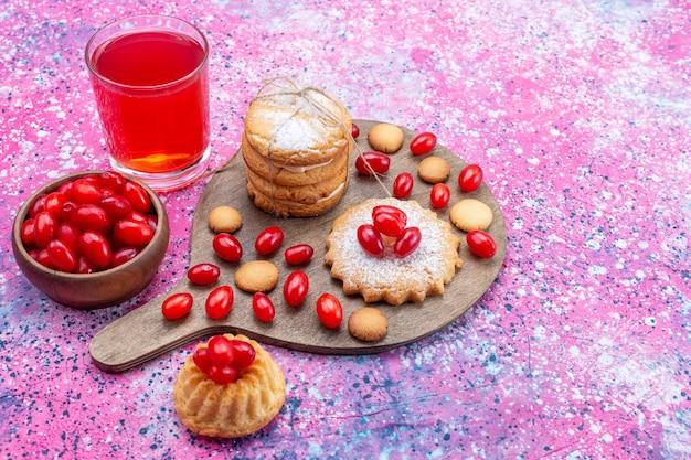 Romige sandwichkoekjes met kornoeljessap van rode kornoeljes op heldere, koekjescake koekje zoetzure fruitbes