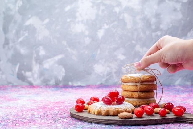 Romige sandwichkoekjes met rode kornoeljes op heldere, koekjescake koekje zoetzure fruitbes