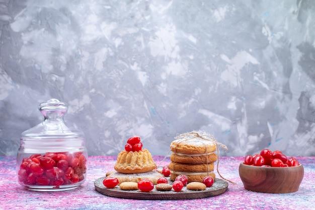 Romige sandwichkoekjes met rode verse kornoeljon helder bureau, koekjescake koekje zoetzure fruitbes