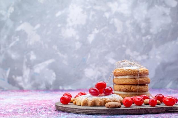 Romige sandwichkoekjes met verse rode kornoeljes op heldere, koekjescake biscuit zoetzure fruitbes