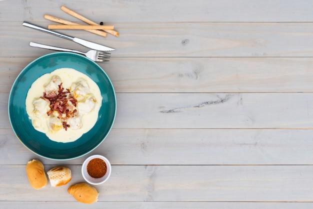 Romige smakelijke italiaanse deegwaren in ceramische plaat met brood voor maaltijd op houten achtergrond