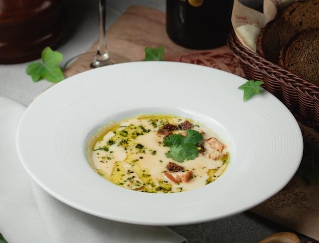 Romige soep met kruiden en oliesaus.