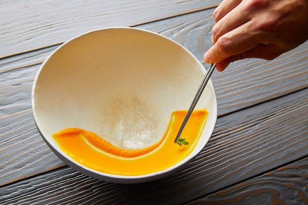 Romige wortelcreme die op witte kom wordt geschilderd