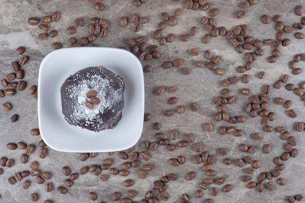 Rommel van koffiebonen rond een kleine schaal met een met chocolade bedekte cake op een marmeren oppervlak