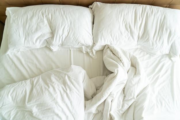 Rommelig bed met wit kussen en deken op bed